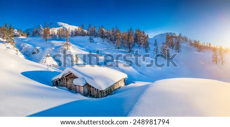 Panoramic view of beautiful winter mountain landscape with snow capped mountain cabin in the Alps in golden evening light at sunset - stock photo