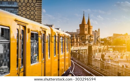 Panoramic view of Berliner U-Bahn with Oberbaum Bridge in the background in golden evening light at sunset with retro vintage Instagram style hipster filter effect, Berlin Friedrichshain-Kreuzberg - stock photo