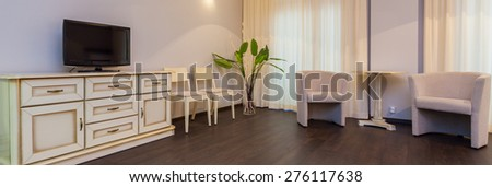 Panoramic view of bright and elegant room with a commode