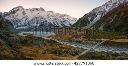 Panoramic View Of Cloudy And Overcast Autumn View At Hooker Valley Track, Mount Cook National Park With Suspension Bridge Crossing Hooker Lake And  Mount Sefton In The Background - stock photo