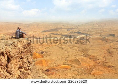 Panoramic view of color sand stone Negev desert and man watching down from cliff. National geological park HaMakhtesh HaGadol - Large Crater - a geological erosion land form, Israel  - stock photo