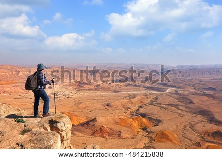 Panoramic view of color stone desert of Negev and traveler on the mountain top. National geological park HaMakhtesh HaGadol - Large Crater - a geological erosion land form, Israel