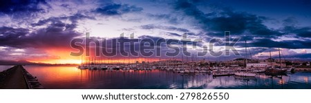 Panoramic view of colorful cloudy sunset in the port of Cagliari - despite being a backlight is all lighted properly, is everything in focus from the horizon to the boats - stock photo