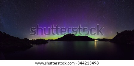 panoramic view of colorful northern lights (Aurora Borealis) at fjord landscape, Norway, Europe
