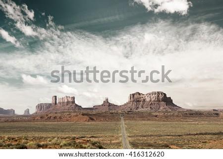 panoramic view of desert highway toward monument valley  - stock photo