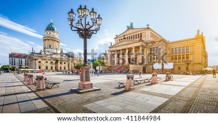 Panoramic view of famous Gendarmenmarkt square with Berlin Concert Hall and German Cathedral in golden evening light at sunset with blue sky and clouds in summer, Berlin Mitte district, Germany - stock photo