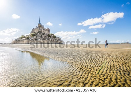 Panoramic view of famous historic Le Mont Saint-Michel tidal island with male tourist taking a photograph on a sunny day with blue sky and clouds in summer, Normandy, northern France - stock photo