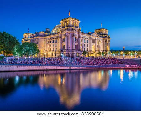 Panoramic view of famous Reichstag building, seat of the German Parliament (Deutscher Bundestag), with Spree river in twilight during blue hour at dusk, Berlin Mitte district, Germany - stock photo