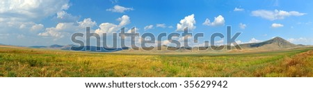 panoramic view of fields and mountains in summer - stock photo