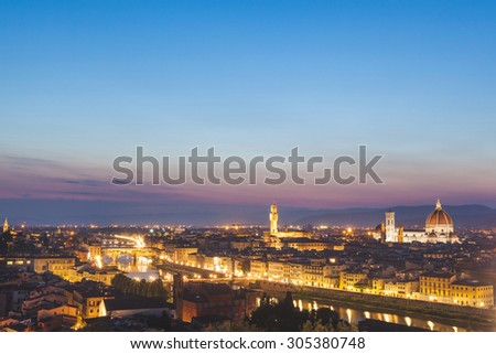 Panoramic view of Florence at dusk. From left to right there are Ponte Vecchio, Palazzo Vecchio and Santa Maria del Fiore cathedral. Photo taken at dusk, with blue sky.