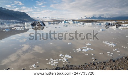 Panoramic view of glacier tongue, lake and mountains in Iceland - stock photo