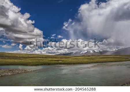Panoramic view of high mountains. Meadow with green grass and river under blue sky with light clouds - stock photo