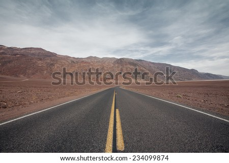 panoramic view of hot summer road through the death valley, nevada - stock photo