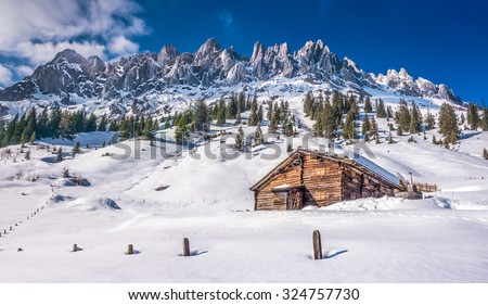 Panoramic view of idyllic winter wonderland with mountain tops and traditional mountain chalet in the Alps on a sunny day with blue sky, Muhlbach am Hochkonig skiing resort, Salzburger Land, Austria - stock photo