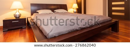 Panoramic view of illuminated bedroom with wooden bed - stock photo