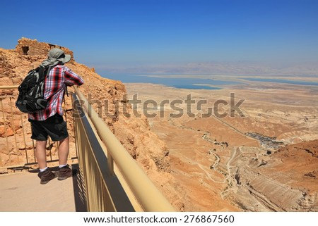 Panoramic view of Judaean Desert and Dead See from Masada ancient fortification  and man watching down from cliff. Masada fortification of the 1st century, popular sight ,UNESCO World Heritage,Israel  - stock photo