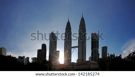 Panoramic view of Kuala Lumpur city center skyline with tall silhouette skyscrapers against a sparkling sunset. - stock photo