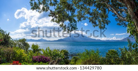 Panoramic view of Lake Atitlan and Toliman Volcano (Guatemala) from a lush tropical garden - stock photo