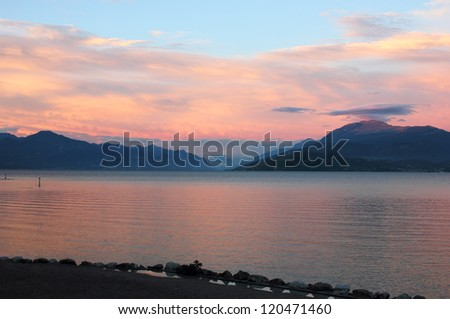 Panoramic view of Lake Garda, with colorful sunset over the mountains. Shot near the coast of Sirmione. - stock photo