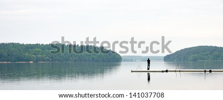 Panoramic view of lake with man fishing from jetty
