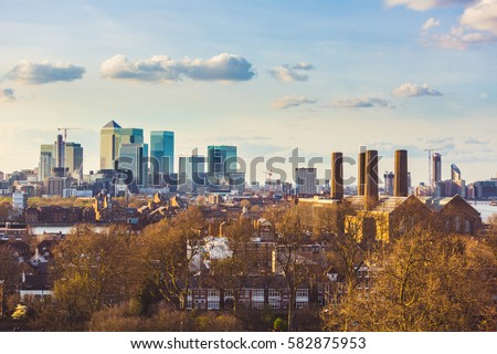 Panoramic view of London from Greenwich park at sunset. Residential buildings and houses on foreground, modern buildings on background. Architecture and travel concepts