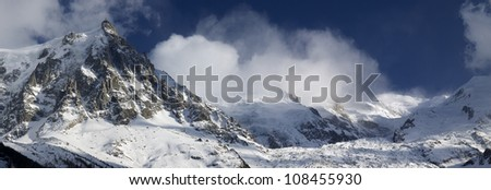 Panoramic view of Mont Blanc. On the left the Aiguille du Midi and right, sunlit, notably the Mont Blanc, Chamonix, Alps, Mont Blanc Massif, France - stock photo
