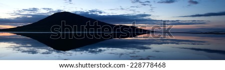 Panoramic view of mountain and sky reflected in tidal lake, Scotland - stock photo