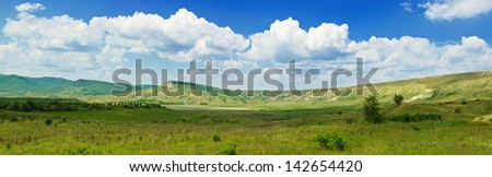 Panoramic view of mountain summer landscape with clouds and green hills (Crimea)