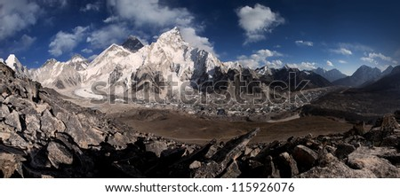 Panoramic view of Mt Everest from Kala Patthar in dry landscape with snow capped himalayas and blue sky, and rocky foreground.