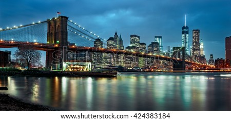 Panoramic view of New York City Manhattan downtown at night from the Brooklyn Bridge and skyscrapers