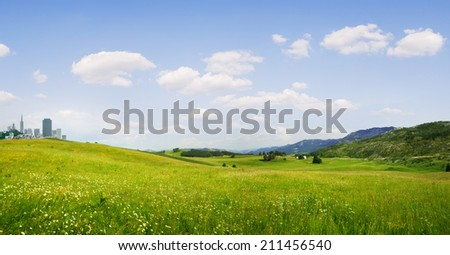 panoramic view of nice green hill and city  on blue sky background - stock photo