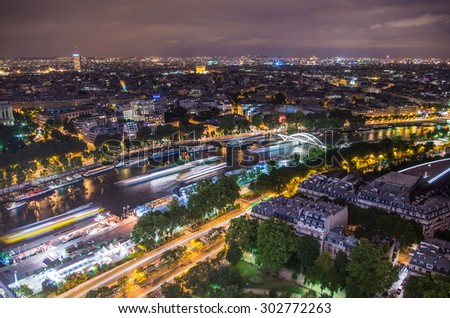 Panoramic view of Paris city from Eiffel tower in moonlit night with light traced from ships moving along Seine river