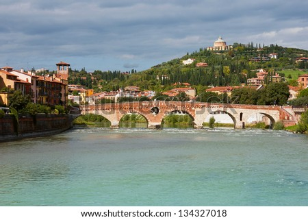 Panoramic view of Ponte Pietra in Verona, Italy in a bright sunny day with dramatic clouds at the background. - stock photo