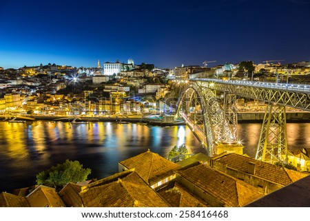 Panoramic view of Porto and the Dom Luiz bridge in Portugal at night - stock photo