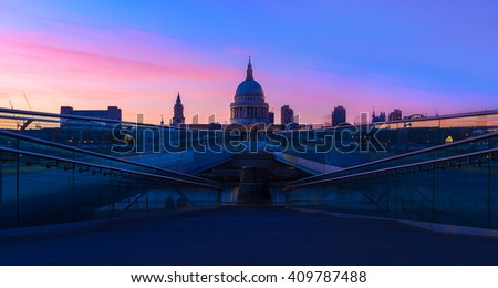 Panoramic view of purple sunset at St Paul's Cathedral and the Millennium Bridge in London with people walking in blurred motion