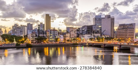 Panoramic view of Recife in Pernambuco, Brazil showcasing its historic architecture by the Capibaribe River at sunset.