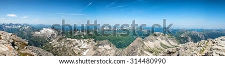 Panoramic View of Remote German Alpine Mountains Stretching into Distant Horizon on Sunny Day with Blue Sky - stock photo