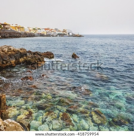 Panoramic view of rocky ocean coast with views of the coastal city with port and the waves crashing on the rocks