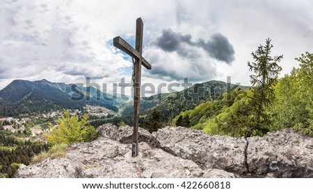 Panoramic view of Romanian town Baile Tusnad in Carpathian mountains from cliff with large wooden cross - stock photo