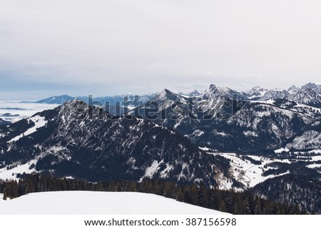 Panoramic view of rugged alpine peaks and valleys under snow in winter on a misty overcast cold day in an aerial overview from a plateau - stock photo