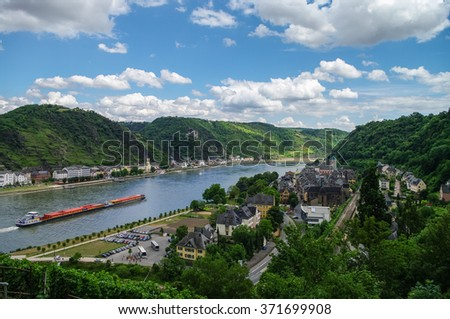 Panoramic view of Sank-Goar and Snak Goarshausen medival village and Rhine vineyards on slope of the hills in Germany. Cargo ship sails on the Rhine river. - stock photo
