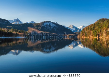 Panoramic view of scenic idyllic winter landscape in the Bavarian Alps at famous mountain lake Alpsee, Fussen, Allgau, Upper Bavaria, Germany - stock photo