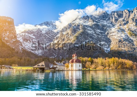 Panoramic view of scenic mountain scenery with Lake Konigssee with famous Sankt Bartholomae pilgrimage church in golden evening light in fall, national park Berchtesgadener Land, Bavaria, Germany - stock photo