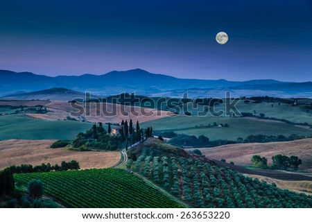 Panoramic view of scenic Tuscany landscape with rolling hills and valleys in beautiful moonlight at dawn, Val d'Orcia, Italy - stock photo
