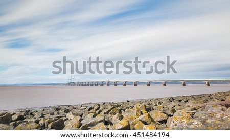 Panoramic view of Second Severn crossing, a bridge linking Bristol to Wales. Long exposure image with smooth water and blurred clouds. Travel and time concepts. - stock photo