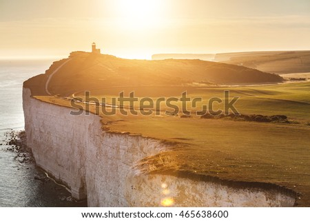 Panoramic view of Seven Sisters cliffs with lighthouse and sea on background at sunset. Photo taken from Beachy Head, on Eastbourne side, with backlight sunset. Travel and nature concepts.