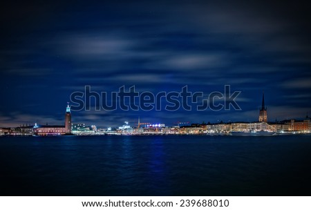 Panoramic view of Stockholm cityscape during night with the Town hall (Stadshuset) and Riddarholmen Church, filters apllied for a blue cold effect. - stock photo