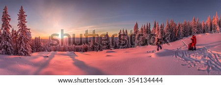 Panoramic view of sunset in the snowy mountains, with two skiers and tourists on the slope - stock photo