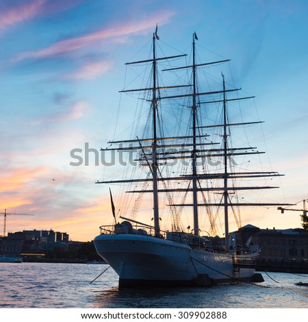 Panoramic view of swedish capital Stockholm in sunset. Silhouette of large traditional wooden sailboat and old medieval downtown of Gamla stan in the background. Copy space. Square composition.