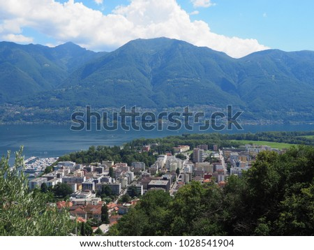 Panoramic view of swiss travel city of LOCARNO in SWITZERLAND, alpine Lake Maggiore landscapes with yacht haven, buildings on Alps slopes, cloudy blue sky in 2017 warm sunny summer day, Europe on July